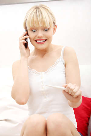 Pregnancy test - happy woman on phone, positive result Stock Photo - 9298799