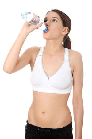 Beautiful young woman in sport clothes with bottle of mineral water  photo