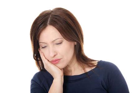 dent douleur: Femme s�duisante dans sa quarantaine appuyant sur sa joue meurtris avec une expression douloureuse, comme si elle a un mal de dent terrible.
