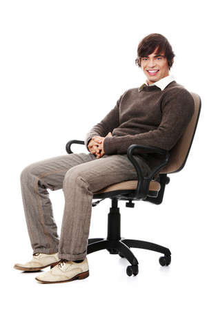 Young happy man sitting on a wheel chair, isolated over a white background . Stock Photo - 9713771