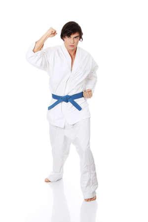 Karate. Man in a kimono , isolated on the white background  photo