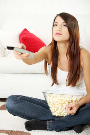 Girl watching TV having fun eating popcorn. photo