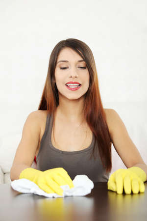 Young woman cleaning furniture table in yellow gloves Stock Photo - 9713762