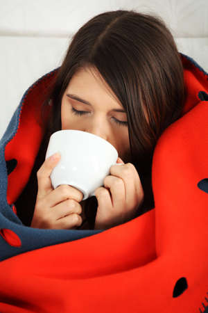 freeze: Young woman caught cold, wrapped up in blanket, drinking something hot from cup.