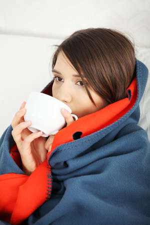 Young woman caught cold, wrapped up in blanket, drinking something hot from cup.  photo