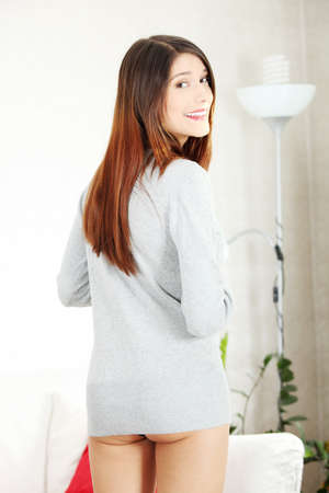 Sexy playful woman in long sweater at home  photo
