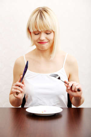 Woman eating nutritional supplement - pills on plate. photo