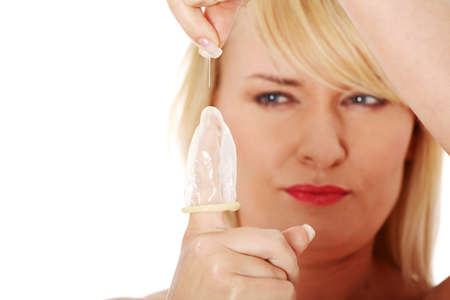 birth prevention: Mature woman making hole in condom with needle.