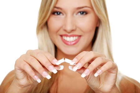 fumando: Joven hermosa rubia sonriente mujer romper cigarrillos, aislado en blanco Foto de archivo