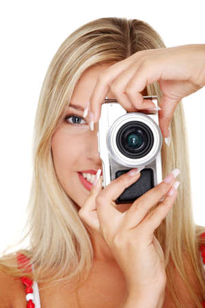 Young beautiful smiling blond woman holding a micro four thirds photo camera. Isolated over white background. photo