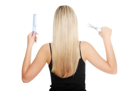 Young blond woman holding hairdressers tools , isolated on white photo