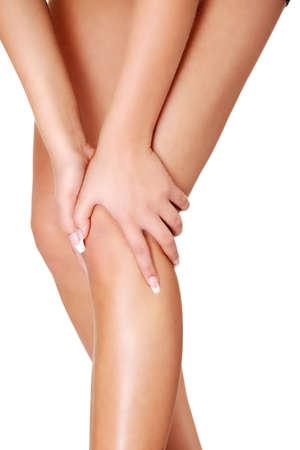 Молодая женщина вздымалась травмы ноги, изолированных на белом Фото со стока