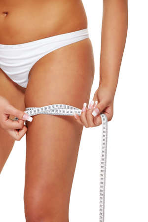 elasticity: Closeup photo of a Caucasian womans leg. She is measuring her thigh with a white metric tape measure after a diet