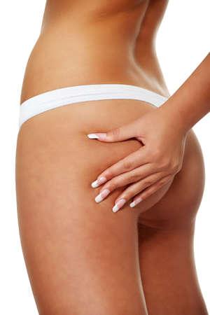 cintura perfecta: Una ni�a en ropa interior blanca comprobaci�n celulitis en su trasero, aislado en un fondo blanco  Foto de archivo