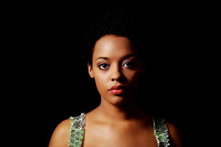 Portrait of beautiful serious afro american woman over black background photo