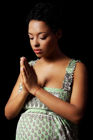 Young beautiful afro american pregnant woman praying against black background photo