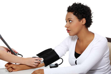 Doctor checking blood pressure of pregnant woman, isolated on white background photo
