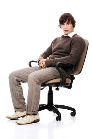 sitting: Young casual man on a chair, isolated on white  Stock Photo