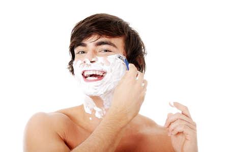 shaving blade: Portrait of young handsome man shaving