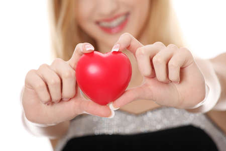 Beautiful young casual woman holding red heart, isolated on white  photo