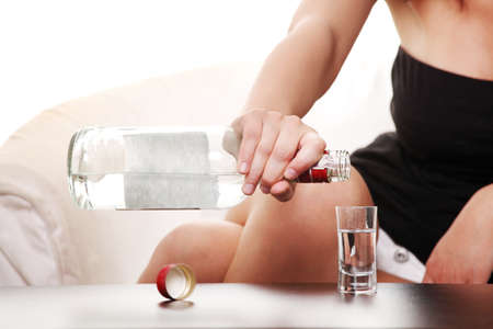 vodka: Young sad woman in depression, drinking alcohol (vodka)  Stock Photo