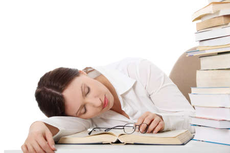 Pretty caucasian girl sleeping on her book near pile of books photo
