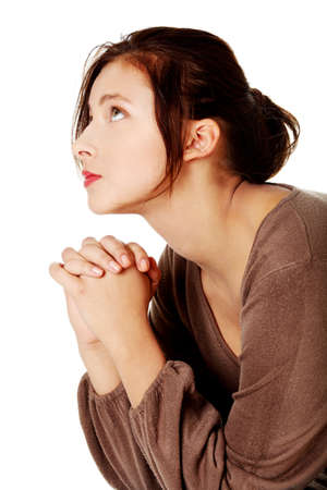 Young caucasian girl praying and looking up. photo