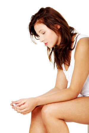 Young caucasian girl sitting and checking her pregnant test. photo