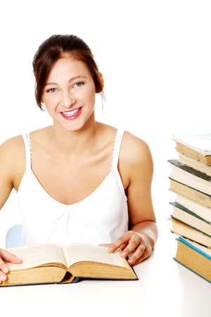 Young caucasian girl smiling and sitting near the pile of books over whire background. photo