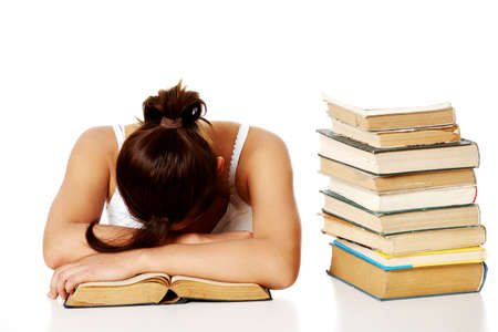 Young pretty caucasain girl sleeping on the desk with her head on the book  near the pile of books. photo