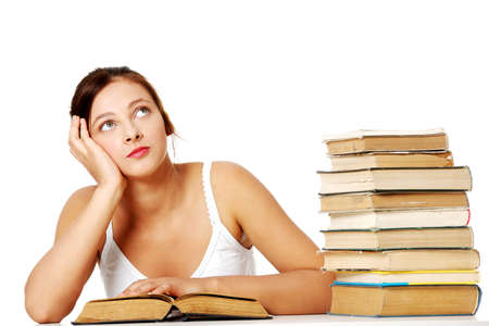 Young girl sitting with book near the pile of books and thinking. Isoalted on white. Stock Photo - 11253865