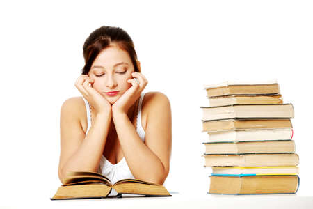 Young pretty caucasain girl sitting and reading a book near the pile of books. photo
