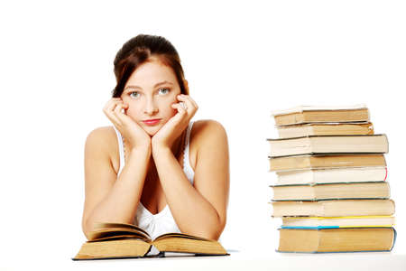 Young pretty caucasian girl holding her head, sitting near the pile of books and thinking. photo
