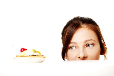 Young caucasian girl hiding behing the desk and looking at the cake over white.  Stock Photo - 11253851