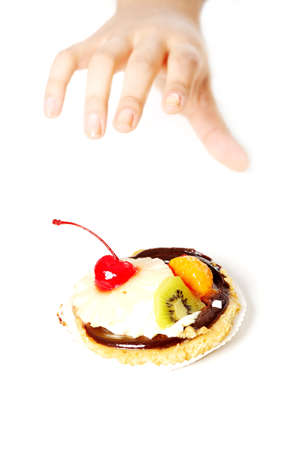 Hand reaching for a cake over white background. photo
