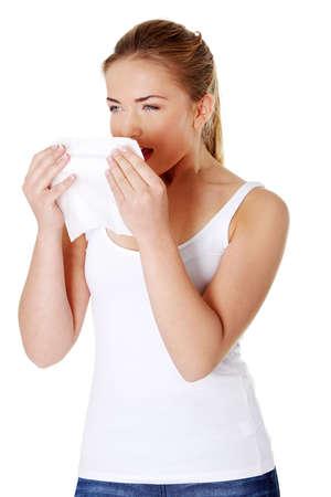 estornudo: Chica rubia joven estornudos y la celebraci�n de los tejidos. Foto de archivo