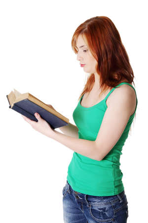 Pretty standing caucasian teen girl reading a book. Isolated on white. Stock Photo - 11254166