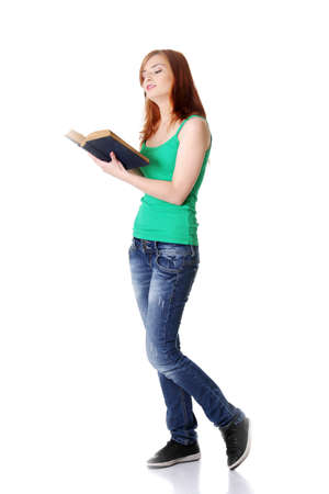 Pretty standing caucasian teen girl reading a book. Isolated on white. Stock Photo - 11253924