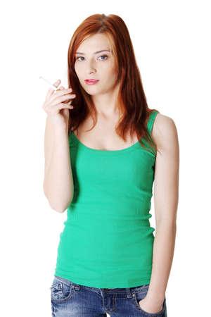 malign: Pretty caucasian standing teen girl holding cigarette. Stock Photo