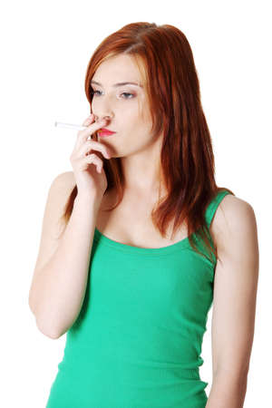Pretty standing teen caucasian smoking girl. Isolated on white background.  photo