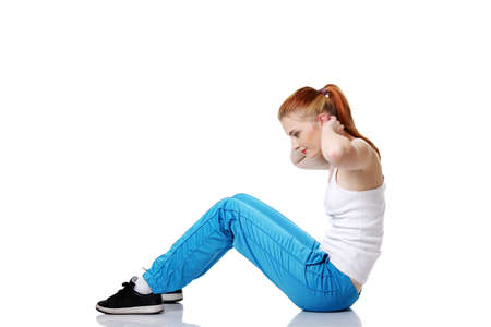 Beautiful caucasian teen girl doing exercises on the floor over white. Stock Photo - 11253915