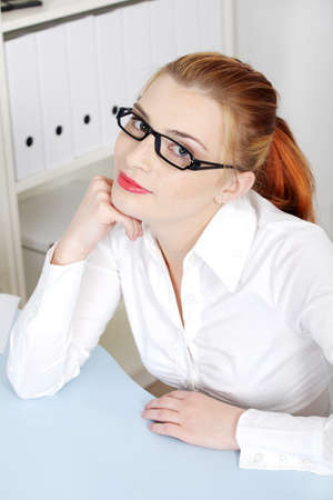 Pretty caucasian woman in glasses sitting behind the desk. photo