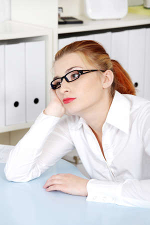 Beautiful caucasian woman in glasses thinking and sitting in the office. photo