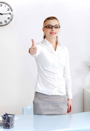 Young caucasian woman standing in the office showing okay gesture. photo