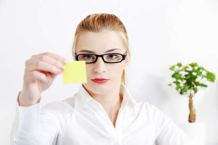 Young caucasian bussineswoman looking at yellow sheet of paper in the office. photo