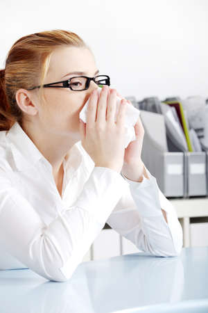 Caucasian woman in glasses sneezing in the office. photo