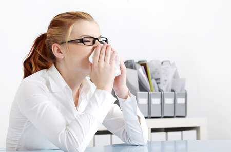 Caucasian busnesswoman in glasses sneezing in the office. photo