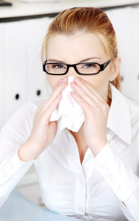 Young woman sneezing in the office. photo