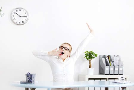 Blonde caucasian businesswoman in glasses yawning in the office. Stock Photo - 11253926