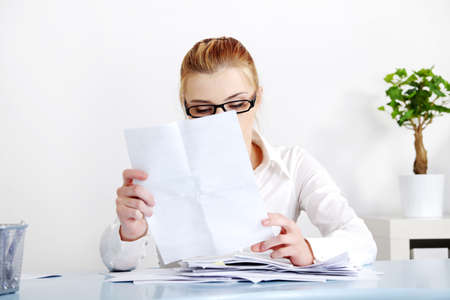 Sitting caucasian woman in glasses reading files behind the desk. photo